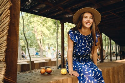 Gorgeous smiling girl in dress and hat happily sitting on wooden fence in city park
