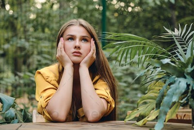Sad brown haired girl in yellow shirt leaning head on hands looking up among green leaves