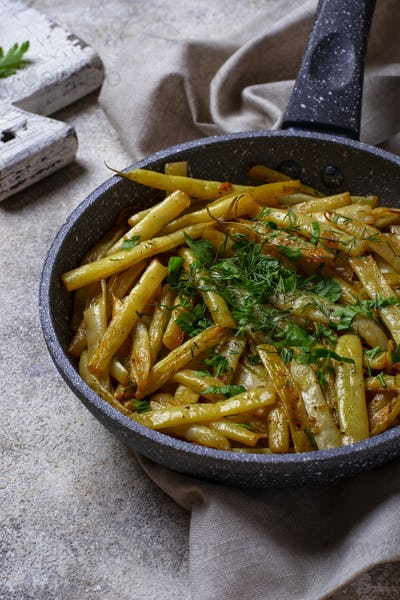 Stewed yellow wax beans in pan