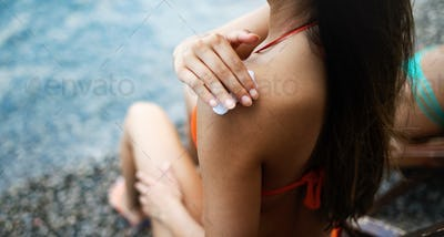 Close up photo of a young woman applying sunscreen protection cream