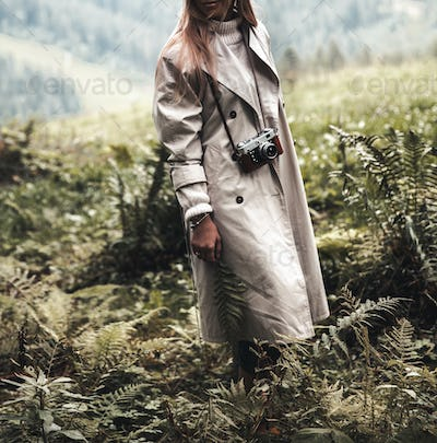 Beautiful woman in a beige raincoat in the mountains in a forest area. Nature fashion