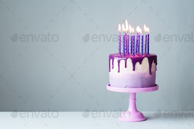 Birthday cake with drip icing and purple candles