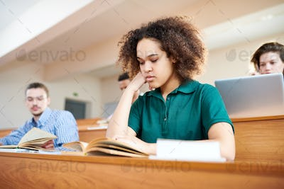 Concentrated African-American student reading textbook