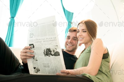 Positive young couple reading news together