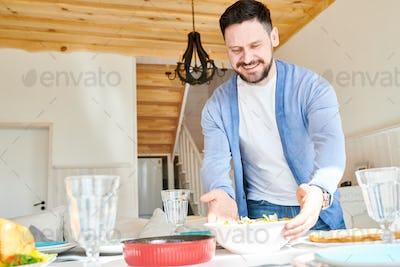 Happy Mature Man Setting Table