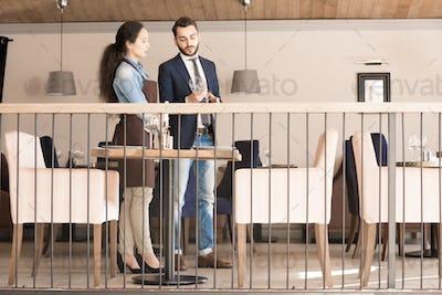 Professional restaurant manager teaching new waitress