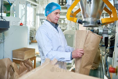 Senior Factory Worker Working at Packaging Line