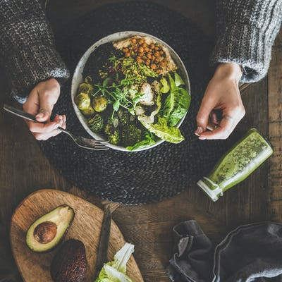 Flat-lay of healthy superbowl, smoothie and womans hands, square crop