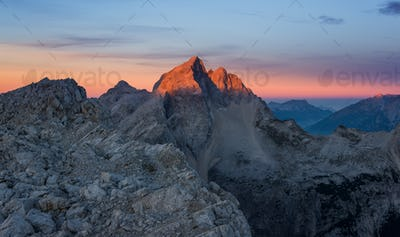 Mount Jalovec at sunrise glows in vivid colors