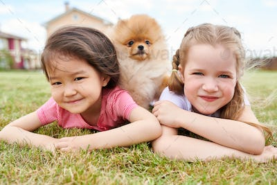Two Little Girls Posing with Puppy Outdoors