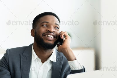 Glad african businessman talking on cellphone at office