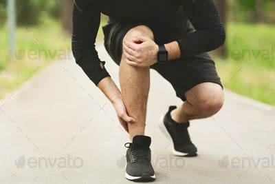 Male runner is suffering from ankle pain on jogging