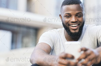 Handsome african man making selfie and smiling outdoor