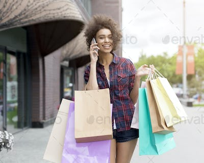 Afro girl holding colorful paper bags, talking by phone
