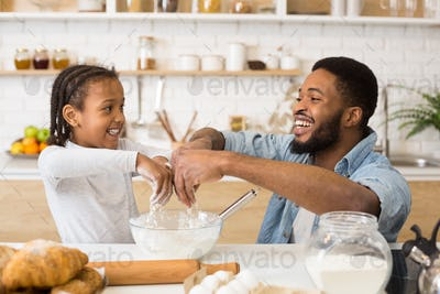 Cute afro girl making dough with her father, pouring flour