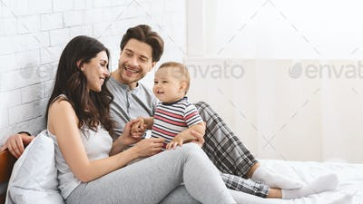 Happy millennial couple enjoying parenthood with adorable baby