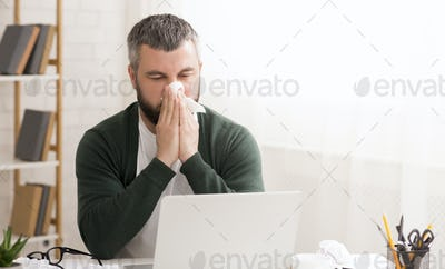 Caucasian man has runny nose, working from home