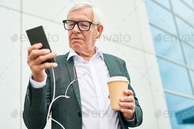 Elderly entrepreneur with drink using smartphone