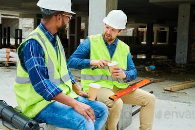 Puzzled worker talking to colleague about building project