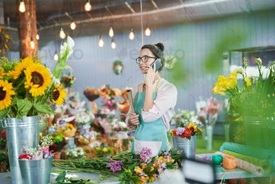 Florist Talking by Smartphone in Shop