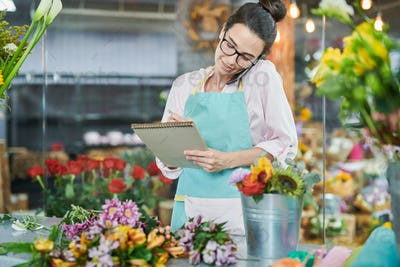 Florist writing notes talking by smartphone
