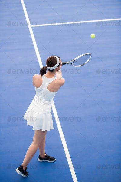Woman  Serving Ball in Tennis Court