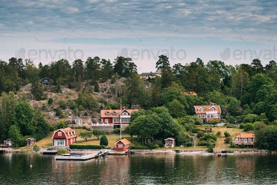 Sweden. Beautiful Red Swedish Wooden Log Cabin House On Rocky Is