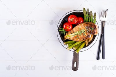 Grilled chicken breast on a cast iron skillet with grill vegetables on a wooden background, flat lay