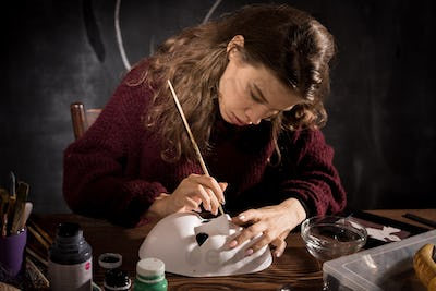 Concentrated woman making mask