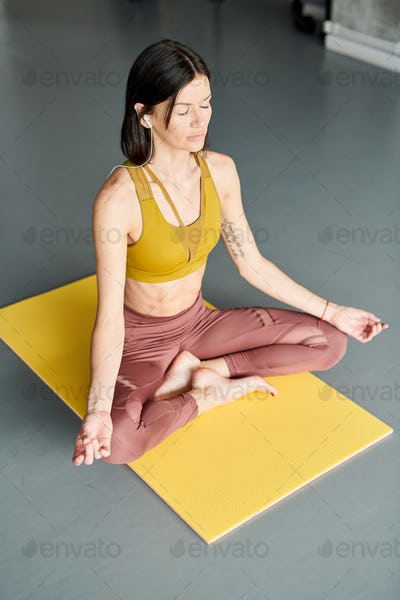Young Woman Meditating in Gym