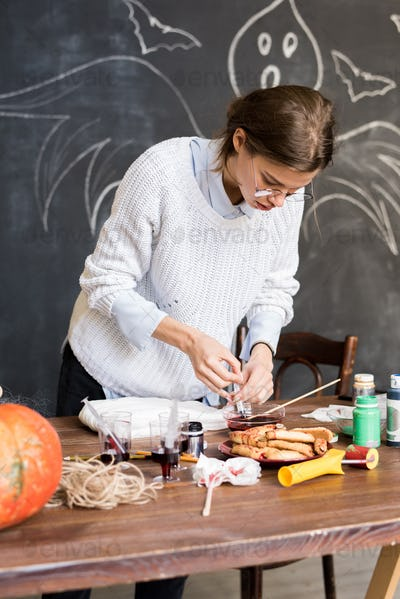 Woman drawing up liquid paint in syringe