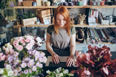 Pretty florist working with social media of flower shop