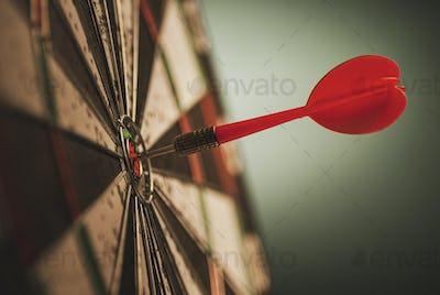 Successful bulls eye centre dart on a target