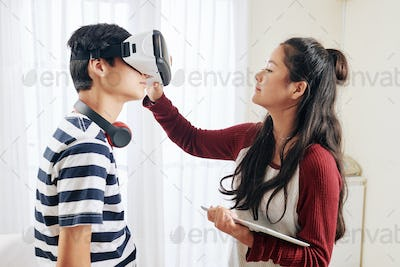 Girl helping to wear vr glasses