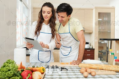 Woman showing recipe to her boyfriend