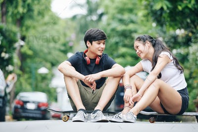 Mixed-race teenage brother and sister sitting outdoors