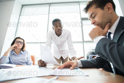 African manager asking staff about mistake at meeting