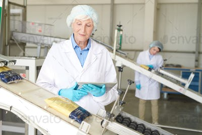 Senior Woman Controlling  Packaging Line