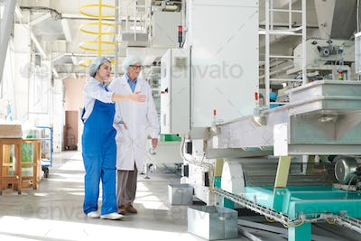 Young Woman Presenting Factory Equipment