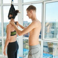 Yoga trainer assisting woman in neck stretcher