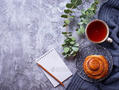 Feminine workspace with bun, cup of tea and notebook