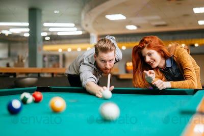 Beautiful couple playing billiards