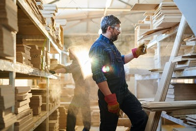 Serious furniture worker finding detail at warehouse