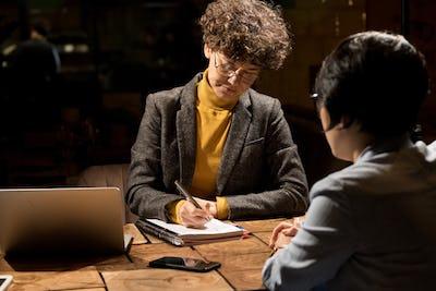 Business ladies writing plan of work in dark office