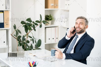 Cheerful businessman communicating on mobile phone
