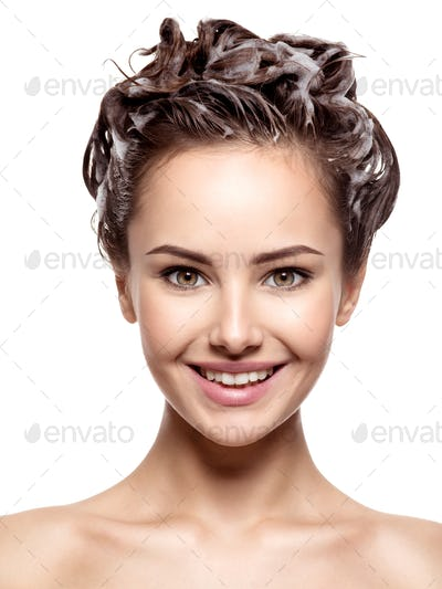 Beautiful smiling woman soaping the hair