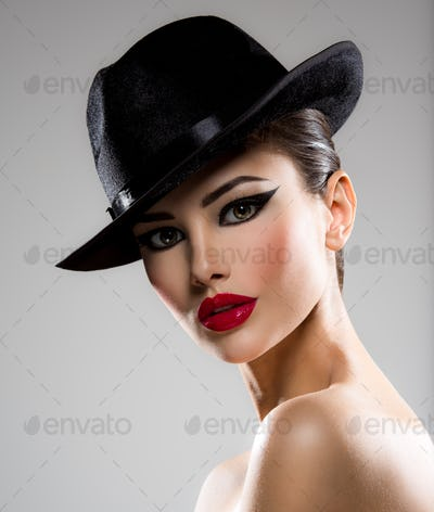 Сlose-up portrait of a woman in a black hat  with red lips