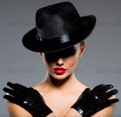Сlose-up portrait of a woman in a black hat and gloves with red