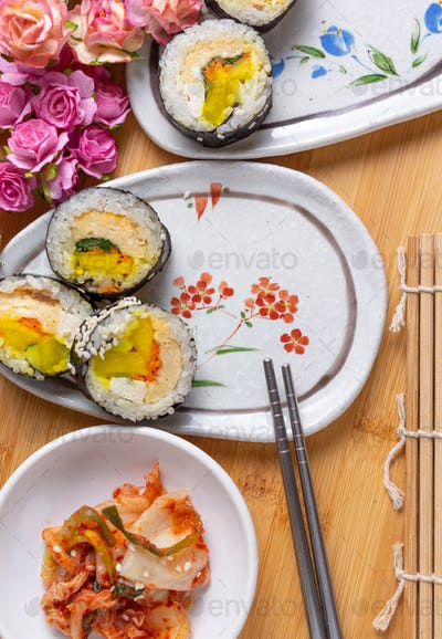 Kimchi and Gimbap serving on white plate
