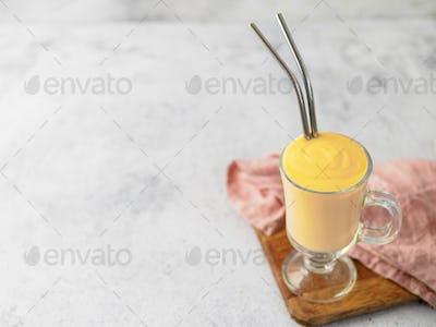 Yellow milkshake with metal straws, sopy space